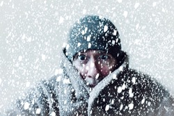 Wintery scene of shivering man in snowstorm or ice storm