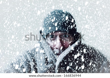 Wintery scene of shivering man in snowstorm or ice storm  #166836944