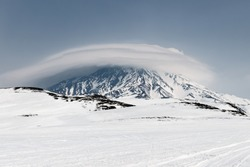 Wintry mountain landscape of Kamchatka Peninsula: view of snowy active Koryak Volcano (Koryakskaya Sopka) and beautiful lenticular clouds in cloudy weather. Eurasia, Russian Far East, Kamchatka Region