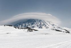 Wintry mountain landscape of Kamchatka Peninsula: view of snowy active Koryak Volcano (Koryakskaya Sopka) and beautiful lenticular clouds in cloudy weather. Eurasia, Russian Far East, Kamchatka Region