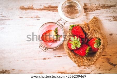 Wiosenne owoce, truskawki w lnianym worku z truskawkowym jogurtem na vintage drewnianym stole. Zdjęcia stock ©