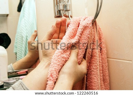 Wipe of hands a terry red towel in a bathroom - stock photo