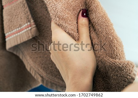 Photo of  Wiping hands with a towel. The concept of care for cleanliness, personal hygiene. Disease prevention. The woman wipes his hands after washing them