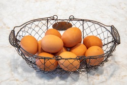 Wire basket of a dozen brown eggs