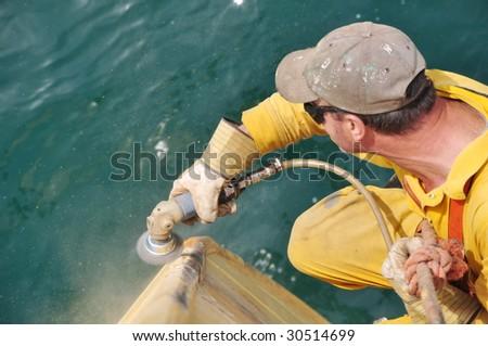 wire brushing of ship's hull - stock photo