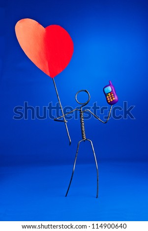 Wire character holding mobile phone and a heart