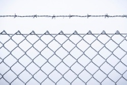 Wire fence covered with frost, close-up. Cold temperature scenery with frozen metal fence. Cold January day in south Germany, in Schwabisch Hall city
