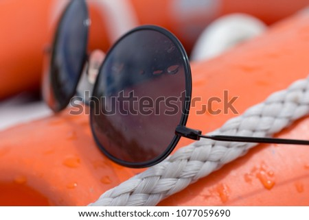 wire frame black sunglasses covered in water droplets placed on board an orange boat buoyancy aid #1077059690