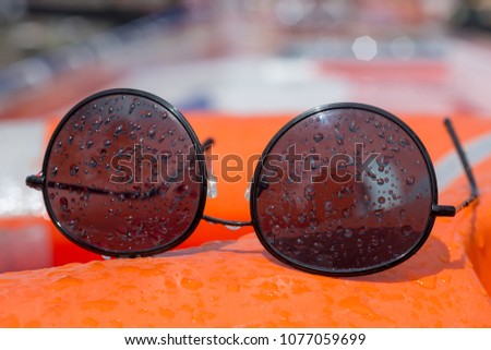 wire frame black sunglasses covered in water droplets resting on board a boat buoyancy aid #1077059699