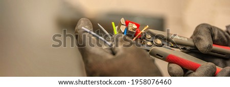 Wire strippers. The electrician cleans the protective insulation from the wire using a wire stripper. The process of connecting wires. close-up Foto stock ©