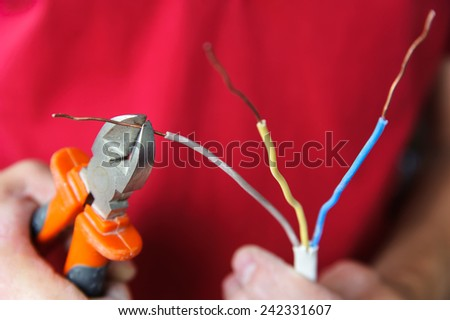 Wire stripping and removing insulation from the live wire of a 3-core cable.