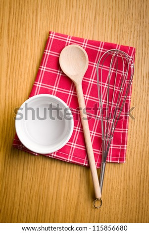 Wire whisk, wooden spoon and ceramic bowl on kitchen table.