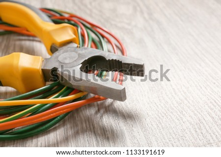 Wire with pliers on wooden floor, closeup