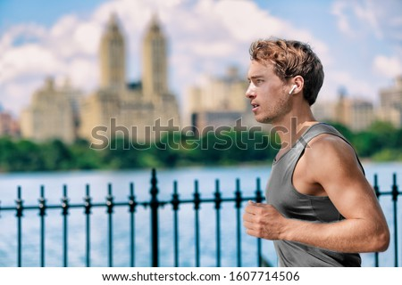 Wireless earbuds man running in Central Park New York city listening to music with wearable technology bluetooth earphone device. Stock photo ©
