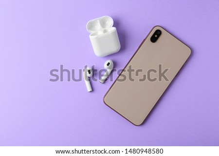Wireless earphones, mobile phone and charging case on violet background, flat lay. Space for text