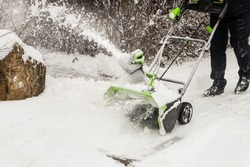 Wireless electric snow blower at work. Rechargeable battery machine.