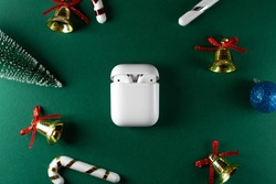 wireless headphones on green christmas background. Airpods. Air Pods. with Wireless Charging Case. entangled 3.5 headphones. Copy Space
