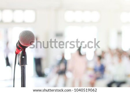 Wireless microphone is placed in front of the stage, there are many people listening to the lecture