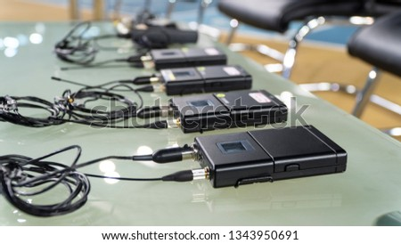 wireless microphone transmitter and wireless microphone reciever on glass table in tv studio
