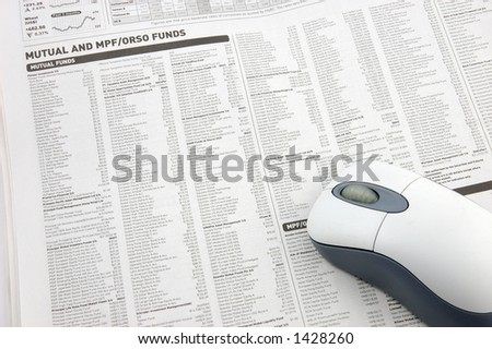 Wireless mouse over mutual funds data on newspaper
