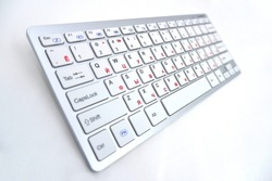 Wireless PC keyboard with Russian layout, keys are red letters, isolated on a white background. Work and write text on a computer keyboard.