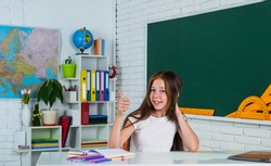 Wisdom. modern education. knowledge day. child pupil sit at table. girl is college student. back to school. teen girl work in classroom near blackboard. cheerful kid learning subject