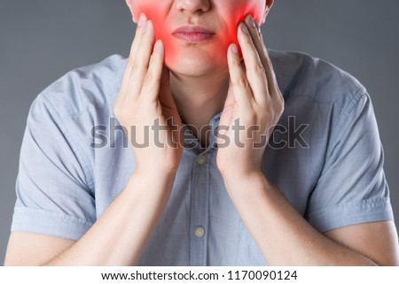 Wisdom teeth, man suffering from a toothache on gray background, painful area highlighted in red #1170090124