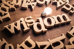 Wisdom word in scattered wood letters with glowing white light bulb, power of wisdom