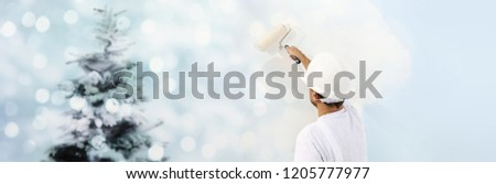 wish a Merry Christmas concept, painter with roller painting a Christmas tree background on a white wall