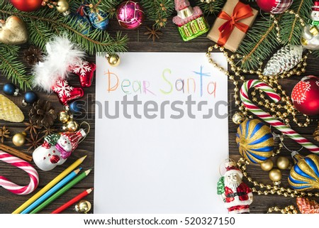 wish card written by kid on wooden desk with many colorful Christmas and new year decoration  #520327150