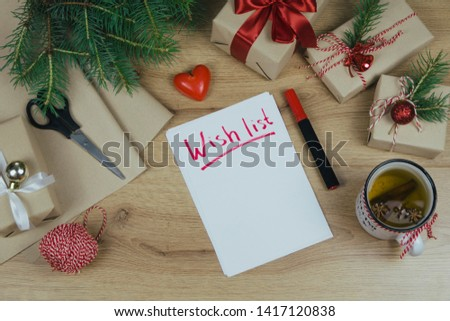Wish list for New Year. Holiday decorations and notebook with wish list on wooden rustic table, flat lay style. Planning concept.