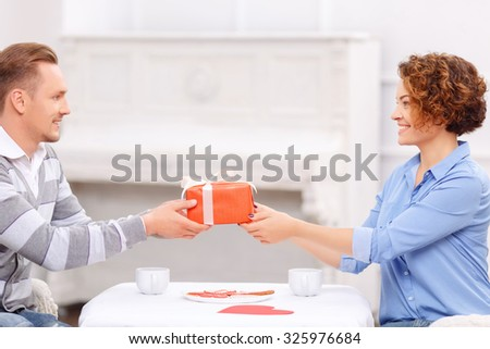 Wish you all the best. Overjoyed handsome man giving present to his girl friend sitting at the table and having dinner.