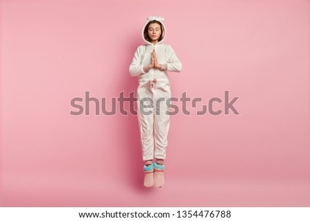 Wishful restful young female jumps in air, wears soft kigurumi costume, keeps palms in praying gesture, prays in morning for good wellness, enjoys good morning, isolated over pink background #1354476788