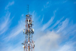 Wispy clouds are seen in the sky behind a tall pylon housing the infrastructure for mobile networks. Antenna send and receive data signals. With copy space