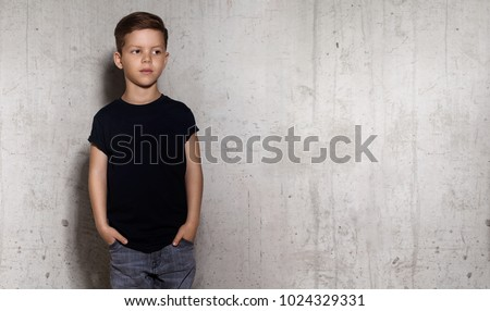 Wistful little guy stands on the wall background and looks away. Portrait of boy in black T-shirt, copy space. Concept of children style and fashion. #1024329331