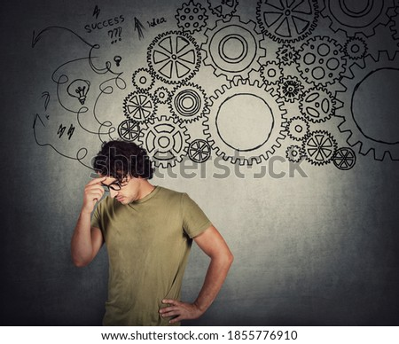 Wistful young man, keeps hand to forehead, hard thinking concept. Different gear cogwheels as metaphor of brain working as a whole mechanism. Search for solutions in mind. Deliberation symbol.