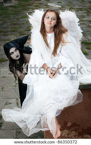 witch and angel against the walls of the old castle