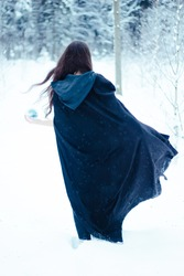 Witch in black cloak with magi? ball