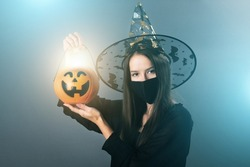 witch in mask at halloween with a burning pumpkin in the hat,trick or treat, sweet terrible autumn holiday,celebration all saints eve