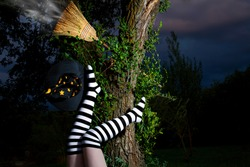 Witch in striped long socks has fallen from her broomstick at night