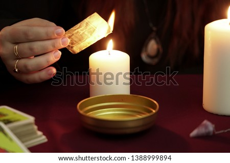 Witch is fortune teller in black mantle doing a magical rite and recites a magic spell. Tarot cards, amethyst stone, white candles on dark background. Occult, esoteric, divination and wicca concept