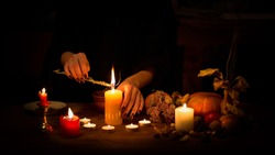 Witch make a spell on the altar in the dark. Female hands with sharp black nails burning magic herb among candles, pumpkin, nuts, dry leaves, selected focus, low key. Halloween, Yule, witchcraft