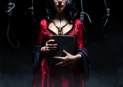 Witch or sorceress with runic makeup and wooden animal skull amulet holding a magic book on dark room background with nooses. Halloween concept.