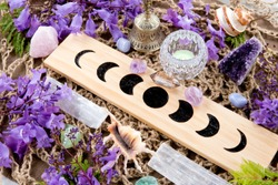 Witch Pagan Moon Phases Altar with crystals of selenite and amethyst, with candle and purple flowers