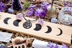 Witch Pagan Moon Phases Altar with crystals of selenite and amethyst, with candle, pentacle and purple flowers
