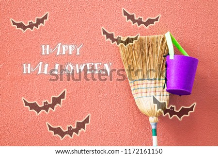 witch's broom and cauldron with bats leaning on the wall, halloween concept #1172161150