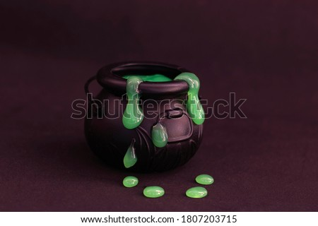 Witch's cauldron on a black background. Green slime flows out of the boiler. Witchcraft, halloween. Stock photo ©
