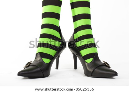 Witch's green and black striped legs with heels together and toes pointing out, white background.