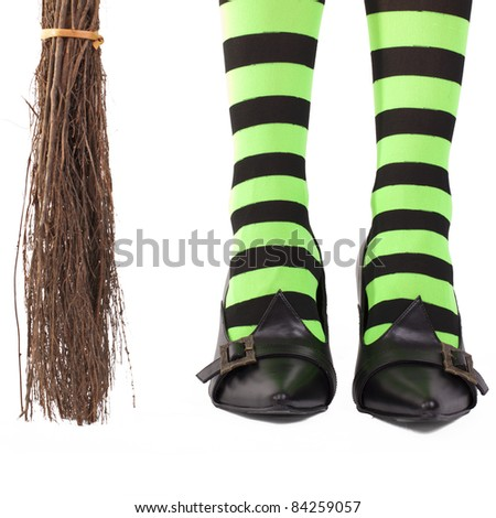 Witch's green and black striped tights and broomstick, white background.