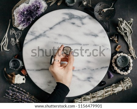 Witch's hand holding Smoky quartz above a marble white round tray. The place for witchcraft with magic things around. View from above. #1156479901